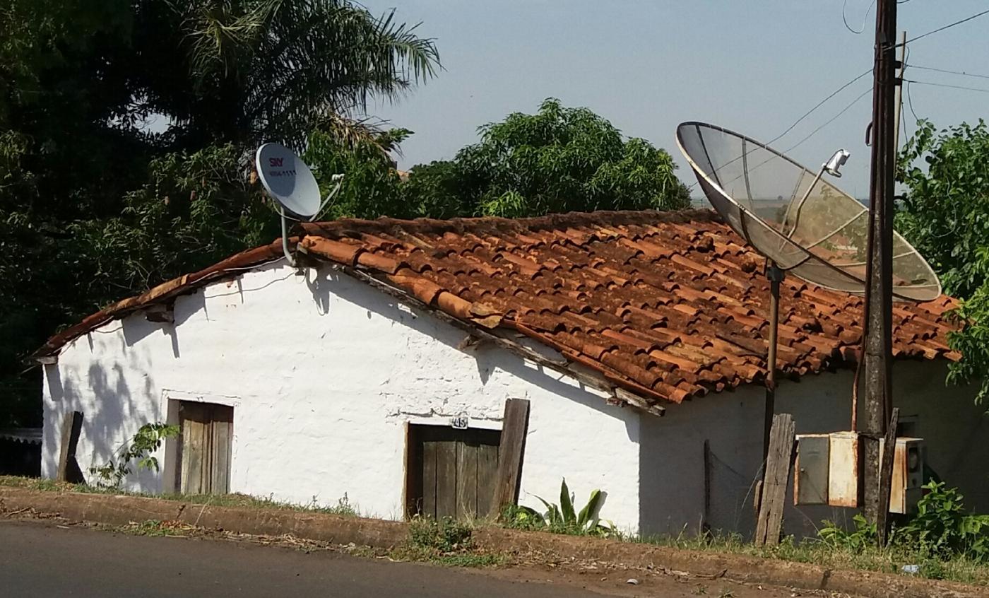 Casa simples em com antena parabólica e TV por assinatura. Noventa e sete por cento dos lares brasileiros têm acesso à TV