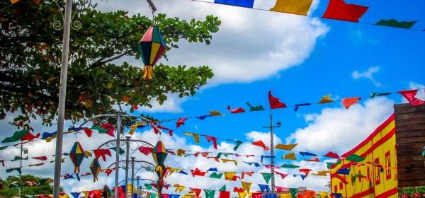 Bandeiras de festa junina penduradas em um espaço público.