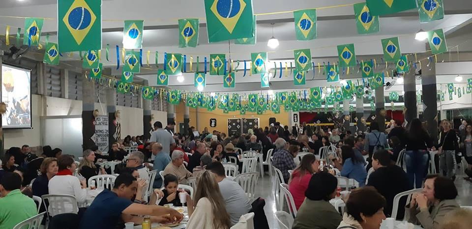 Pessoas sentadas em bancos, comendo as comidas típicas da quermesse de Santo Antônio, em um salão